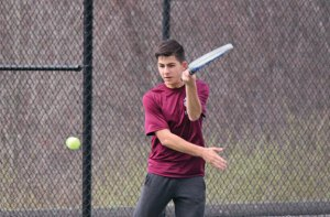 Naugatuck's Marco Rebelo returns a shot during his match versus Woodland's Nick Lucas April 8 in Beacon Falls. –ELIO GUGLIOTTI