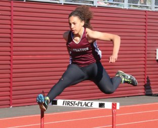 Naugatuck's Jasmine Grey leaps over a hurdle on April 12 during a quad-meet against Waterbury Career, Torrington and Wilby in Naugatuck. Through two meets, the Naugatuck boys and girls teams are 5-1. –LUKE MARSHALL