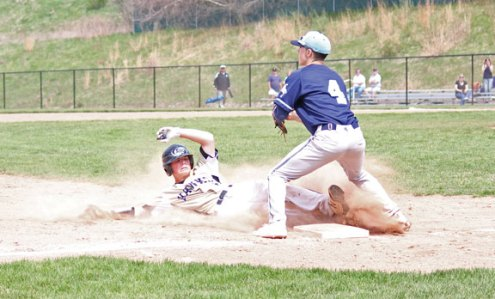 Woodland's Brett Petruny slides safely into third as Ansonia's Jordan Jones (4) guards the base April 22 in Beacon Falls. –ELIO GUGLIOTTI