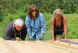 From left, Mike Crane, Theresa Graveline, and Kelly's Kids founder Kelly Cronin work on a chicken coop May 20 at Cronin's farm in Prospect. Volunteers from Home Depot and the Ion Bank Foundation in Naugatuck worked to build a barn and chicken coop to help the nonprofit organization get ready for its first summer camp in July. –LUKE MARSHALL