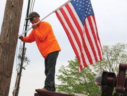 Justin Jones, an employee of the Ed the Treeman, hangs a flag on a utility pole along Route 69 in Prospect May 17. The flags were put on utility poles throughout the center of town along routes 69 and 68. The display, which has been put up every year since 2012 to honor current and former military members, is sponsored by the Prospect Flag Fund. –LUKE MARSHALL