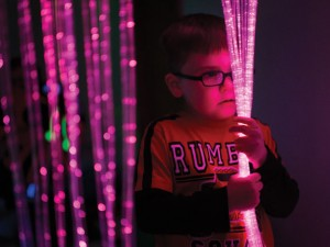 Teddy Salazar, a student at Central Avenue Preschool in Naugatuck, checks out lights inside the school's multi-sensory room. Experts say the therapy aims to calm children and allow them to better focus. –REPUBLICAN-AMERICAN