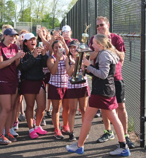 Naugatuck tennis captain Sarah Cook carries the Naugatuck Valley League girls tennis tournament trophy back to her team as her teammates and head coach Jose Sendra cheer May 20 in Beacon Falls. Naugatuck beat Watertown, 4-3, in the final to win the title. –ELIO GUGLIOTTI