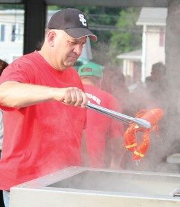 Beacon Falls Firefighter Paul Brennan serves up a steamed lobster during the annual Beacon Hose Firemen's Carnival and Parade last year in Beacon Falls. This year's carnival kicks off June 9. –FILE PHOTO