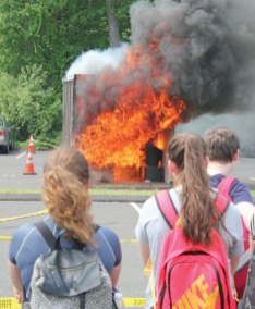 Woodland Regional High School students watch a live fire demonstration May 27 at the school in Beacon Falls. The demonstration was done by Beacon Hose Company No. 1 and conducted by Woodland student Taylor Docimo for her senior project. The project emphasized fire safety and educated students on the importance of smoke detectors and intriguing fire statistics. Power point presentations were shown to every class prior to the demonstration to inform students on the educational reasoning for the project. –ELIO GUGLIOTTI