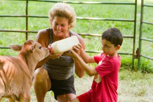 Kelly Cronin, left, helps 5-year-old Steve Cota feed a 4-day-old calf at her farm-based summer camp in Prospect July 20. – Republican-American