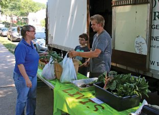 Lisa Mastiani, left, of Waterbury buys vegetables from Noah Pierce, right, and Wyatt Giammattei, both of Livi's Lettuce and Greens in Prospect, during the opening day of the Naugatuck Farmers Market July 6 on the Naugatuck Town Green. The Naugatuck market is open Wednesdays from 10 a.m. until 2 p.m. and Sundays from 9 a.m. until 1 p.m. –LUKE MARSHALL