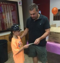 Students from the United Day School in Beacon Falls used money raised during a lemonade stand in July to make care packages for two local soldiers and donated the rest to Beacon Hose Company No. 1. The students raised $400 in total. Pictured, student Nicole Perssico presents a check for $220 to Beacon Hose Fire Chief Jim Trzaski Aug. 2 at the firehouse. –CONTRIBUTED