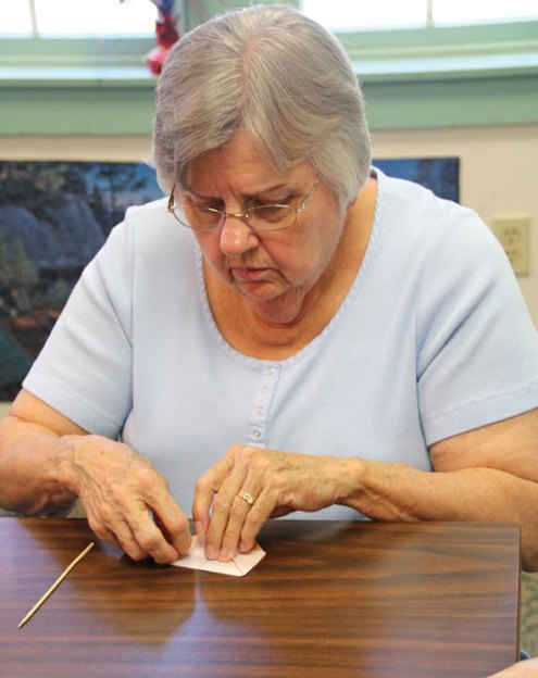 Carol Hodder, of Waterbury, folds an origami heart during a class at the Prospect Senior Center Aug. 4. –LUKE