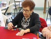 Terri Charette, of Prospect, raises the bet during a hand of Texas Hold'em at the Prospect Senior Center Aug. 4. The senior center hosts poker games regularly for seniors. –LUKE MARSHALL
