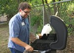 Naugatuck Youth Services Board of Directors Vice President Tom Growth prepares the grill July 20 for the organization's Potluck BBQ celebration at the youth services building on Scott Street. –LUKE MARSHALL