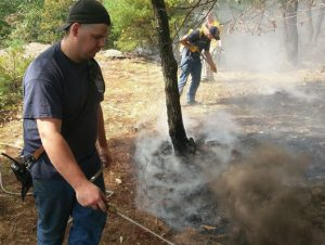 Beacon Falls firefighter Tim Hanks, front, and fellow firefighters work to put out a brush fire in the woods off of Skokorat Road in Beacon Falls Monday. –BEACON HOSE