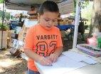 Hunter Ostuni, 5, of Naugatuck draws a picture during the Harvest Moon Festival on the Naugatuck Green on Sept. 17. –LUKE MARSHALL