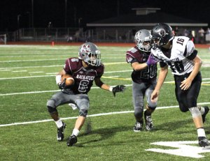 Naugatuck's Elijah Robinson (6) cuts back up field as Jacob Fazekas (20) blocks Torrington's Brandon Reiff (16) Sept. 23 in Naugatuck. Naugatuck won the game, 52-0. –ELIO GUGLIOTTI