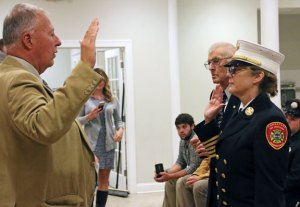 Naugatuck Mayor N. Warren 'Pete' Hess, left, swears in Ellen Murray as Naugatuck's fire chief during a ceremony Oct. 14 in the St. Francis Church hall. –LUKE MARSHALL