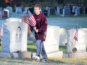 City Hill Middle School seventh-grader James Duda walks in St. James Cemetery in Naugatuck Nov. 1 with an American flag as part of annual program coordinated by local veterans and the school to replace the flags at veterans' graves in the cemetery before Veterans Day. Nearly 1,700 veterans are buried in the cemetery. About 30 middle school students came out to help replace the flags. Students also help replace the flags before Memorial Day. –ELIO GUGLIOTTI