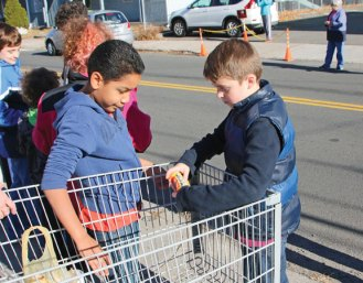 Hop Brook Elementary School students formed a human chain Nov. 18 to pass donated food from the school on Crown Street in Naugatuck to the Naugatuck Ecumenical Food Bank on Spring Street. The food was collected by the students to be donated to the food bank. –LUKE MARSHALL