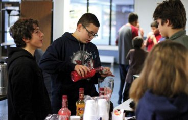 City Hill Middle School eighth-grader Juan Jimenez measures syrup for a slushie as his 'business partner' eighth-grader Brody Moore talks with fellow students waiting to buy a slushie during the school's 'Math Mall' Dec. 23 in Naugatuck. The 'Math Mall' is the culmination of a lesson taught in the real world math class at the school, explained math consultant Rebecca Moore, who teaches the class. Students created a business and learned the math involved with running a business, including expenses, profits and taxes. The students sold their products at the 'Math Mall.' All the 'taxes' generated will be donated to charity, Moore said, and any profits were kept by the students. –ELIO GUGLIOTTI