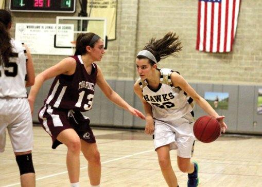 Woodland's Morina Bojka (22) drives to the basket past Torrington's Brie Pergola (13) Monday at Woodland Regional High School in Beacon Falls. Torrington won the game, 41-36. –ELIO GUGLIOTTI