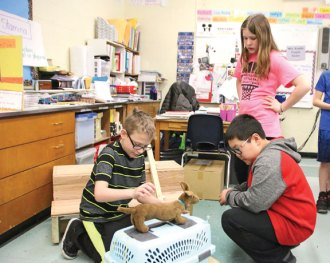 Cross Street Intermediate School fifth-grader Jason Suess, left, explains his invention, the Hot Dog Cart, to sixth-graders Aidan Adanosky, right kneeling, and Stephanie Sutherland on March 9 during the Invention Convention at the school in Naugatuck.