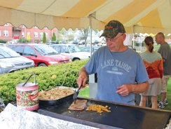 John Rivers cooks up a steak sandwich April 29 on the Naugatuck Town Green during St. Michael Church's Spring Market. The market featured vendors selling handmade crafts in the church, food on the green and a raffle. –LUKE MARSHALL