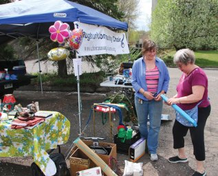 Naugatuck Community Choir President Aldona LaPorta, left, and choir member Linda Ramos look over items the choir was selling during the Naugatuck Exchange Club's White Elephant Sale April 29 at the Naugatuck Event Center downtown. The event, which was a large tag sale, allowed people to rent a table and sell their goods both inside and outside the building. The money raised goes to local charities supported by exchange club. –LUKE MARSHALL