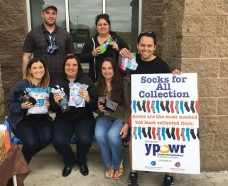 Members of Young Professionals of Waterbury Region hold donations received during the organization's first Sock Collection Drive April 30 at Walmart in Naugatuck. The organization, affiliated with the Waterbury Regional Chamber, collected hundreds of socks for children and adults for Carolyn's Place, the Naugatuck YMCA, the Greater Waterbury YMCA, Naugatuck Youth Services and St. Vincent DePaul Mission of Waterbury. Pictured, in back from left, Douglas Balko of Carmody, Torrance Sandak & Hennessey, and Robyn Ricciardone; front from left, Courtney Ligi, YPOWR program director; Sorrina Salvatore of Ion Bank; Caitlin Sheedy of FD Community Credit Union, and James Higgins of Webster Bank. –CONTRIBUTED