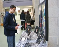 Woodland Regional High School sophomore John D'Amico looks over photographs by fellow student Andrea Hansen on May 25 during the school's annual Summer Fine Arts Night at the school in Beacon Falls. The night featured artwork by students, demonstrations as well as theatrical and musical performances. Kristen Lengyel, a visual arts teacher and chairman of the fine arts department, said about 150 students participated in the event. –LUKE MARSHALL