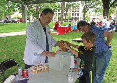 Aidan Petrie, 8, of Naugatuck and his grandmother, Meri Petrie, look over a porous rock held by Neil Berro of the Milford-based education program 'Little Scientists' during a demonstration at the Grace Lutheran Church's 11th annual Earth Day celebration on the Town Green on June 4. –LUKE MARSHALL
