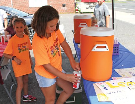Avangeline Magi, 8, of Prospect, fills a cup with lemonade as Abigail Diamanette, 7, of Naugatuck, prepares to fill the next cup during the United Day School's annual lemonade stand Aug. 2 next to the firehouse on North Main Street. The school, which holds runs the stand every year, raised $450 during the sale. The money was donated to Beacon Falls police Officer Caroline O'Bar to help her fill backpacks with school supplies for children in need in the community. O'Bar buys backpacks and school supplies for local children who need them each year. –LUKE MARSHALL