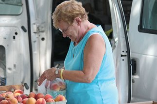 Louise Marcucio, of Marcucio Farms in Ansonia, bags peaches for a customer during the Naugatuck farmers market July 19 on the Green on Church Street. The market is open on Wednesdays from 10 a.m. to 2 p.m. and Sundays from 9 a.m. to 1 p.m. –ELIO GUGLIOTTI