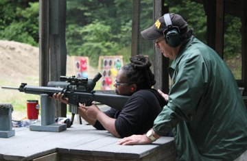Seanda Morgan, of Waterbury, shoots an AR-15 rifle as Mike Carpentieri, a volunteer and certified instructor, watches over her during the Women on Target shooting clinic July 29 at the High Rock Shooting Association's shooting range in the Naugatuck State Forest in Naugatuck. About 30 women attended the clinic, which was divided into two sessions. The clinic was sponsored by the High Rock Shooting Association and the National Rifle Association. The clinic is one of several programs hosted annually by the High Rock Shooting Association. It was open to novice and experienced shooters, and is designed to create opportunities, encourage, educate and mentor women's responsible participation in recreational shooting sports. –ELIO GUGLIOTTI