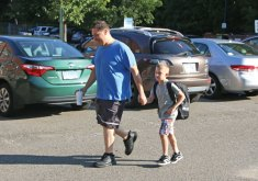 Hop Brook Elementary School second-grader Justin Raimo, 7, walks to school with his father, Terry Raimo, on the first day of school in Naugatuck on Aug. 28. –LUKE MARSHALL