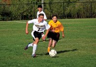 Woodland's Devon Polleta (7) pushes the ball up the field as Sacred Heart's Michael Braun (17) gives chase Oct. 13 at Woodland Regional High School in Beacon Falls. Woodland won the game, 4-1. –ELIO GUGLIOTTI
