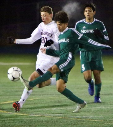 Naugatuck's Justin Barth (20) battles for the ball with Norwalk's Will Gaviria (28) during the Class LL semifinal Monday in Newtown. Naugatuck won the game, 1-0, in overtime. - STEVEN VALENTI/REPUBLICAN-AMERICAN