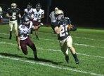 Woodland's Zachariah Kabusk (25) runs the ball past Torrington's Starling Santos (40) Nov. 3 against Torrington at Woodland Regional High School in Beacon Falls. –LUKE MARSHALL