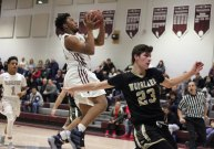 Naugatuck's Latrel Deveaux finishes off a fast break with a basket after shaking off Woodland's Justin Marks (23) Tuesday night at Naugatuck High School. Naugatuck won the game, 69-39.