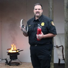 Ed Malaspina, a firefighter and public information officer with the Prospect Volunteer Fire Department, discusses how to put out a grease fire while shooting a public service announcement Oct. 24 at the fire department. –ELIO GUGLIOTTI