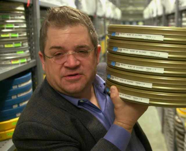 Patton Oswalt with some movie reels.jpg