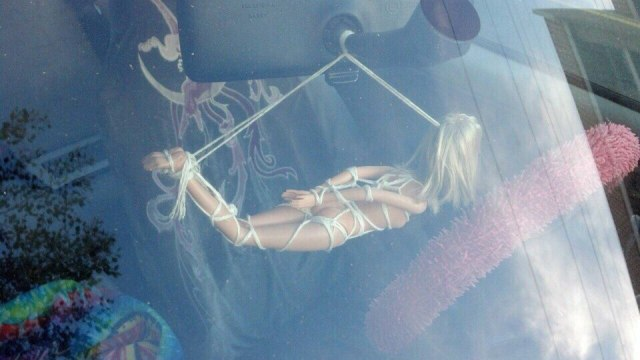 Bondage Barbie hanging from a car.jpg