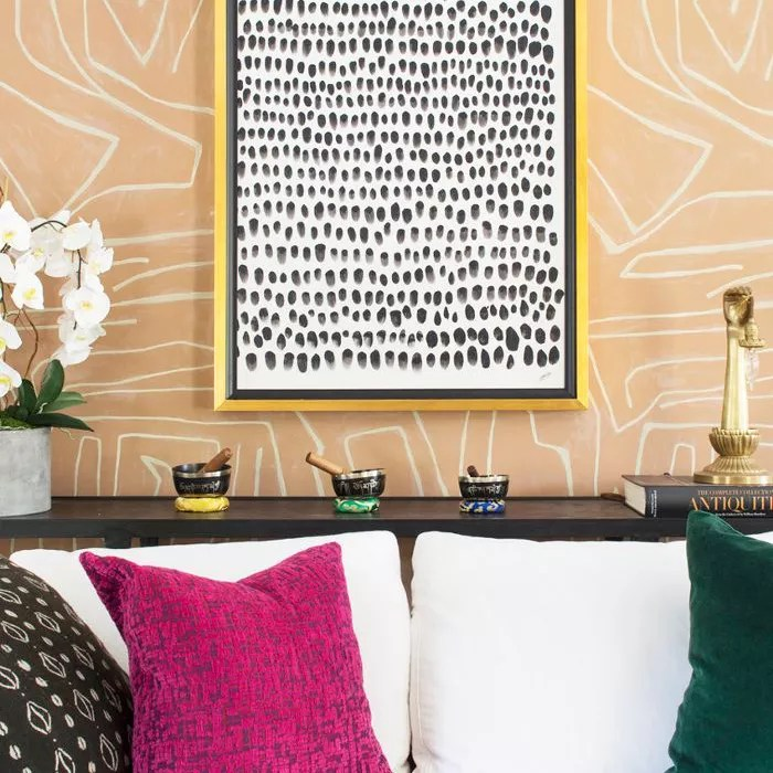 Artwork hangs above a white sofa and patterned wallpaper