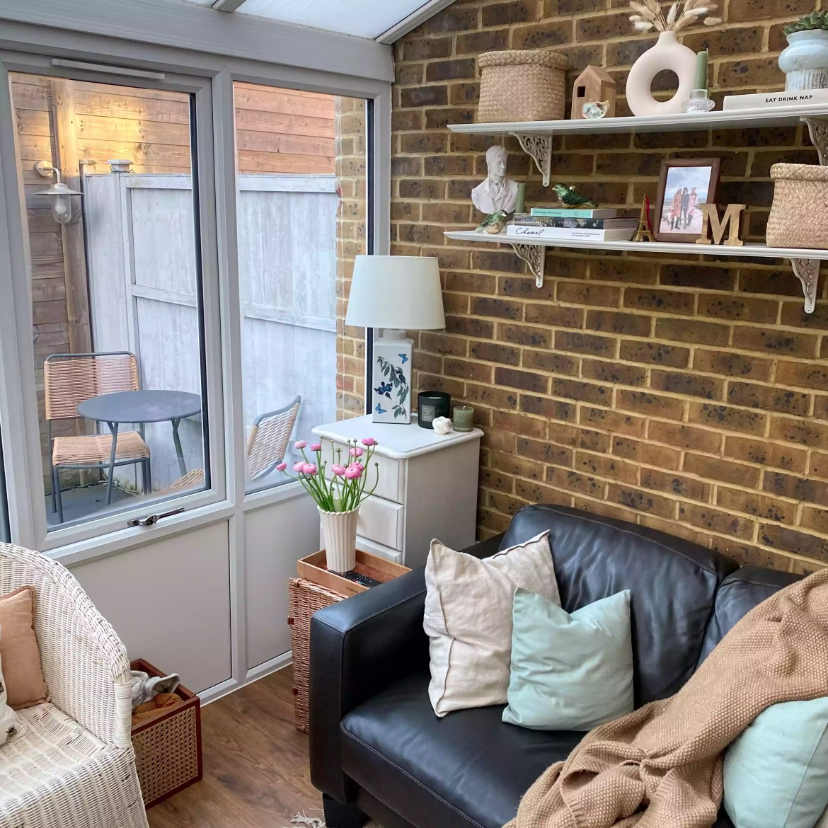 Quaint living room with brick wall and pastel accents.