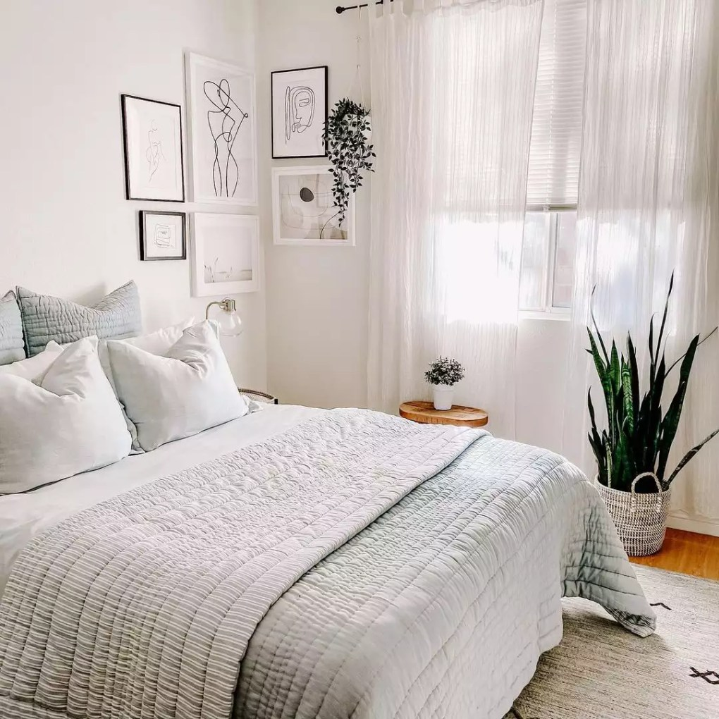 Soft neutral white bedroom with plants.