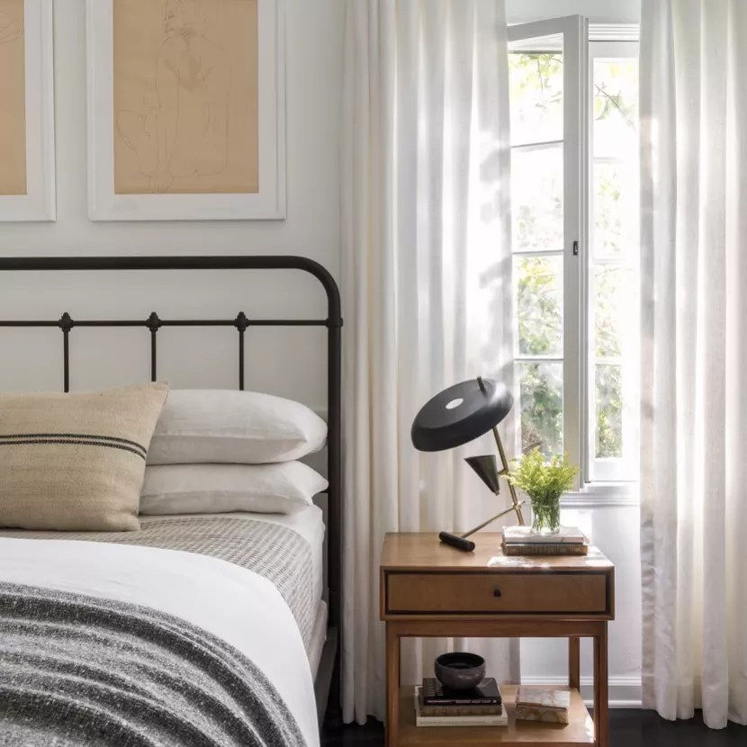 A bedroom with a bold geometric table lamp