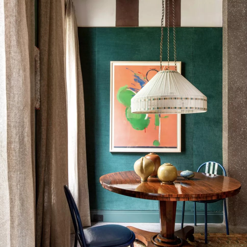 A small kitchen table in a vibrant emerald green room