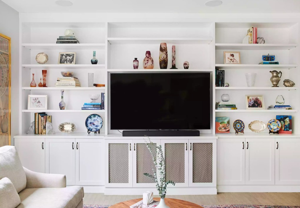 Large wall of white built in shelving with lots of antiques.