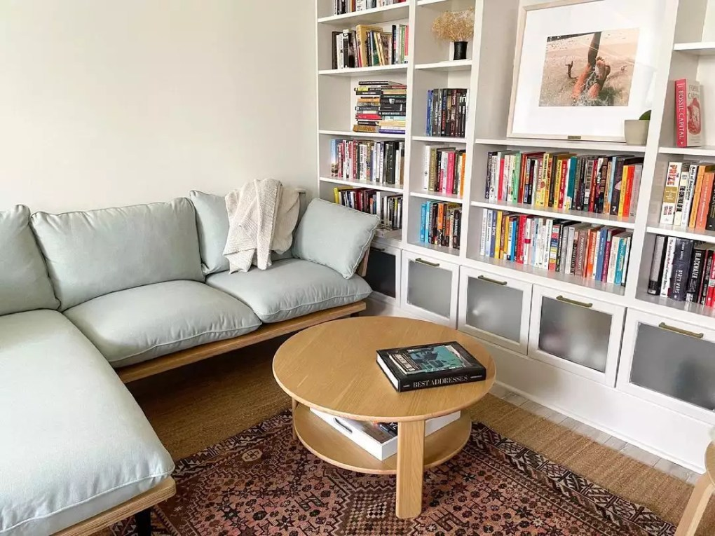 Reading room with full bookshelf and blue couch.