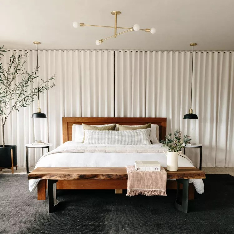 A modern bedroom with sleek pendant lights and a bold geometric chandelier