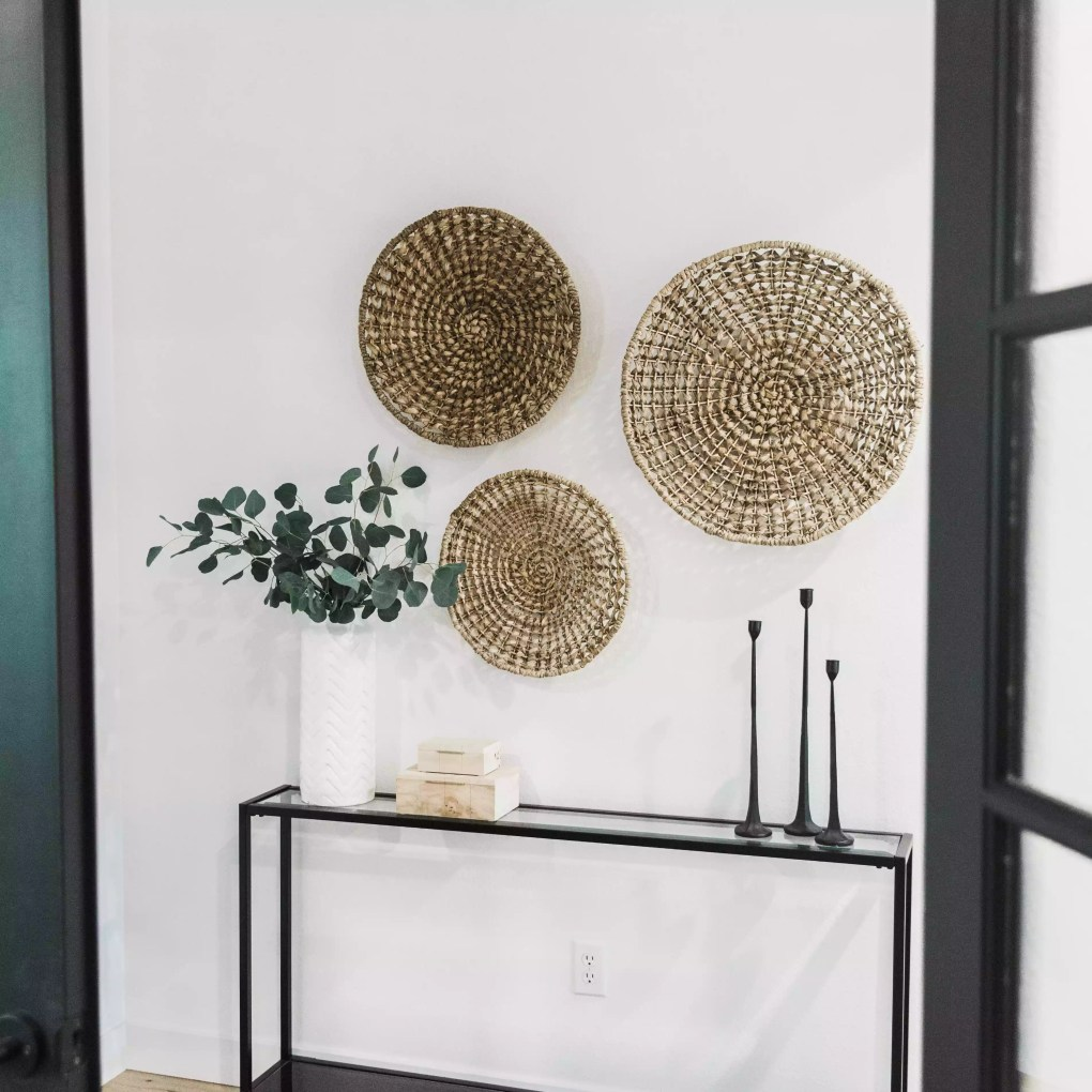 Entryway with woven baskets and black table.
