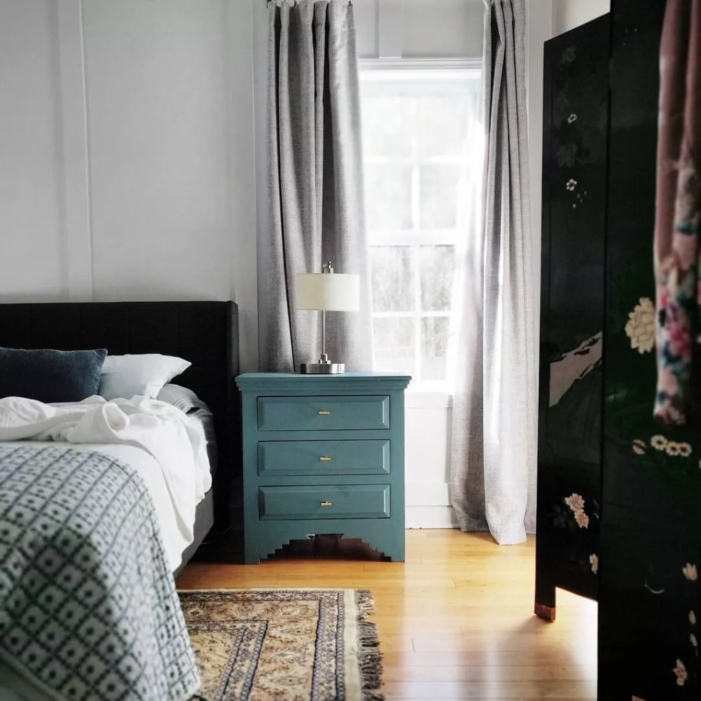 Painted teal dresser in traditional bedroom.